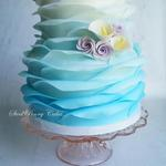 Fondant ruffle wrap in blue ombre with sugar roses and calla lilies.